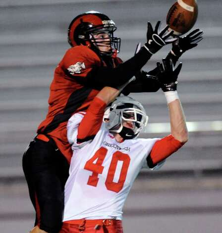 Defensive back Chris Nolan, top, of Bridgeport Central High School breaks up a pass to Taylor Olmstead, # 40 of Greenwich High School during football game between Greenwich High School and Bridgeport Central High School at Kennedy Stadium, Bridgeport, Friday night, Oct. 21, 2011. Photo: Bob Luckey / Greenwich Time
