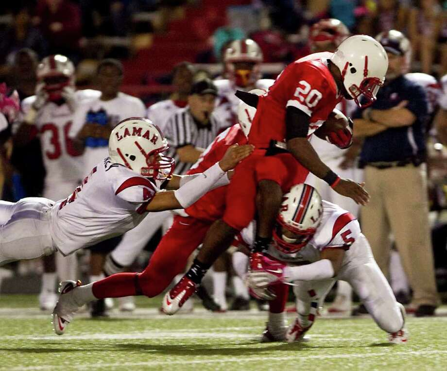 Bellaire High School's Denzel Johnson (20), is slowed down by  breaks up a pass intended for Lamar High School's John Bonney (4) and Daniel Lopez (5) during the first quarter of a 20-5A high school football game, Friday, Oct. 21, 2011, at Butler Stadium  in Houston. Photo: Nick De La Torre, Houston Chronicle / © 2011  Houston Chronicle