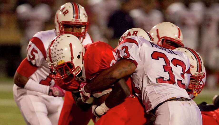 Bellaire High School's Denzel Evans, left, is stopped by Lamar High School's Darion McNeil during the first quarter of his game, Friday, Oct. 21, 2011, at Butler Stadium  in Houston. Photo: Nick De La Torre, Houston Chronicle / © 2011  Houston Chronicle