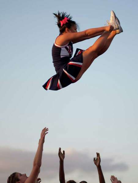 Lizzy Tam, 16, of the Lamar High School cheer squad is thrown into the air by her cheer mates before