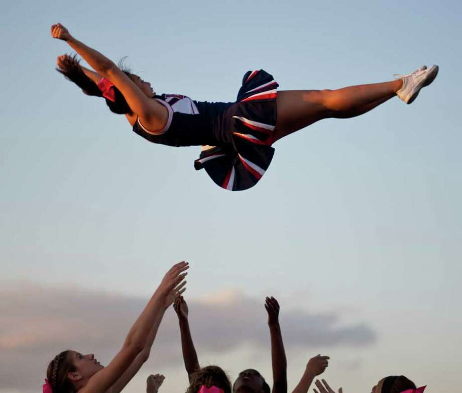 Lizzy Tam, 16, of the Lamar High School cheer squad is thrown into the air by her cheer mates before the Lamar High School versus Bellaire High School football game, Friday, Oct. 21, 2011, at Butler Stadium  in Houston. Photo: Nick De La Torre, Houston Chronicle / © 2011  Houston Chronicle