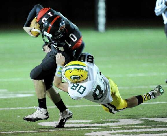 Fairfield Warde QB Chris Foley, # 10, gets tackled by Kevin Epp, # 80 of Trinity Catholic High School during football game between Fairfield Warde High School and Trinity Catholic High School, at Fairfield Warde, Friday night, Oct. 21, 2011. Photo: Bob Luckey / Greenwich Time