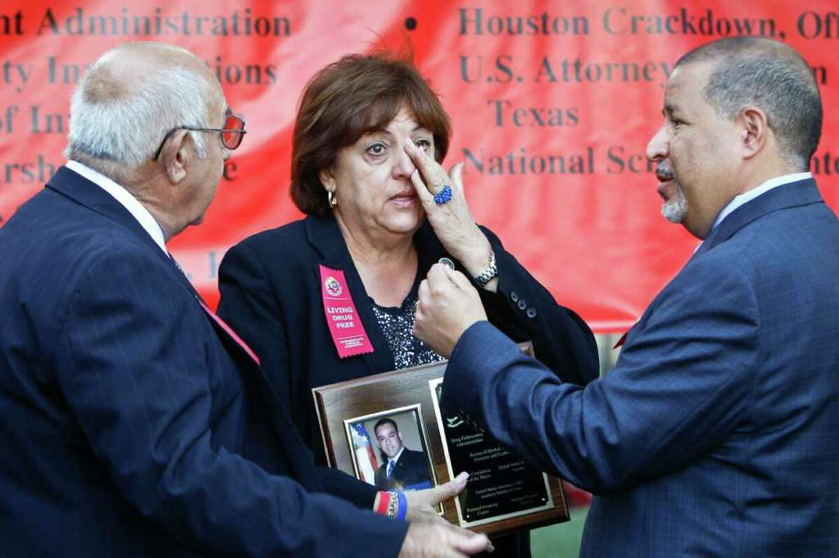 Mary Zapata-Munoz, with her husband, Amador, left, wipes away a tear as she clutches a plaque honoring her son, slain ICE agent Jaime Zapata, in Houston on Friday.