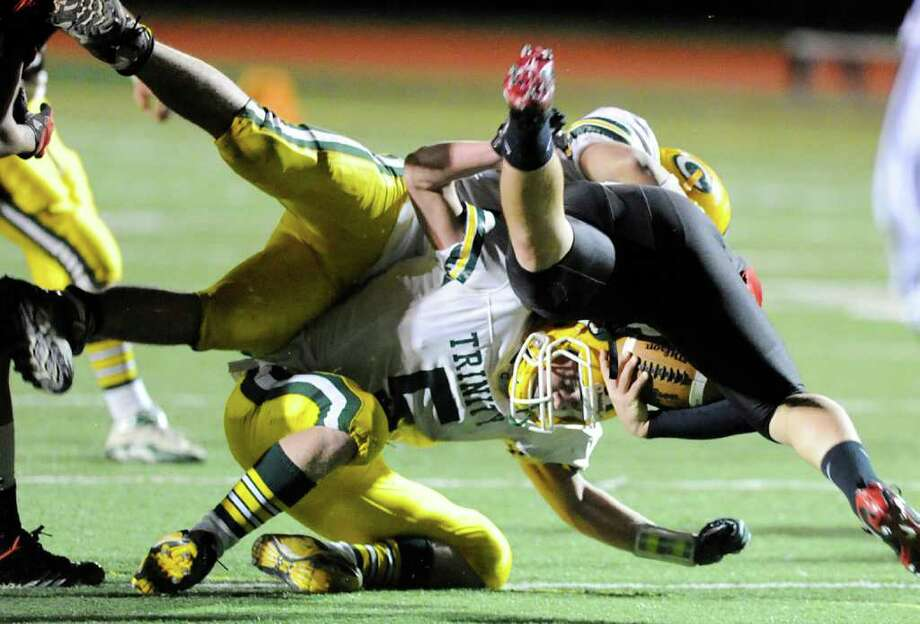 Cody Zaro, # 5 of Trinity Catholic High School, bottom, takes down Max Garrett, # 11 of Fairfield Warde High School on a run during football game between Fairfield Warde High School and Trinity Catholic High School, at Fairfield Warde, Friday night, Oct. 21, 2011. Photo: Bob Luckey / Greenwich Time
