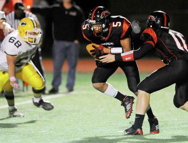 Running back Devon Lofton, # 5 of Fairfield Warde High School takes the hand-off from teammate Chris Foley, # 10, at the start of a 84 yard touchdown run during school football game between Fairfield Warde High School and Trinity Catholic High School, at Fairfield Warde, Friday night, Oct. 21, 2011. Rushing is # 68 George Li, # 68 of Trinity Catholic. Photo: Bob Luckey / Greenwich Time