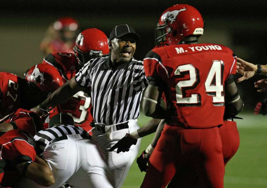 Back Judge Bobby Wright pushes back North Shore's Matthew Young (24) as officials try to determine possession after a fumbled kickoff during the first half of a high school football game against La Porte, Friday, October 21, 2011 at Galena Park Stadium in Houston. North Shore recovered the fumble, and scored a touchdown on the ensuing drive. Photo: Eric Christian Smith, For The Chronicle