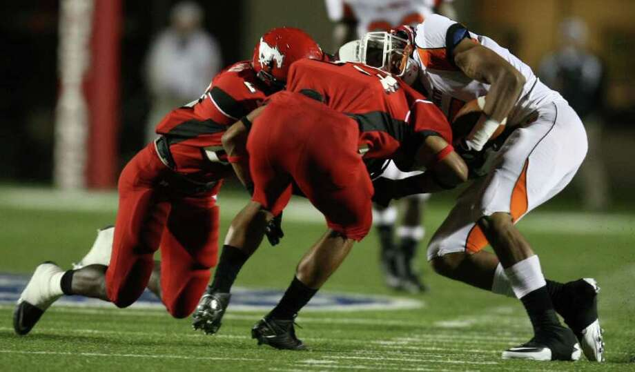 La Porte's Aaron Nance-Garrett (right) is hit by North Shore's Jacoby Walker (center) resulting in a 15-yard personal foul penalty on Walker for helmet-to-helmet contact during the first half of a high school football game, Friday, October 21, 2011 at Galena Park Stadium in Houston. Photo: Eric Christian Smith, For The Chronicle