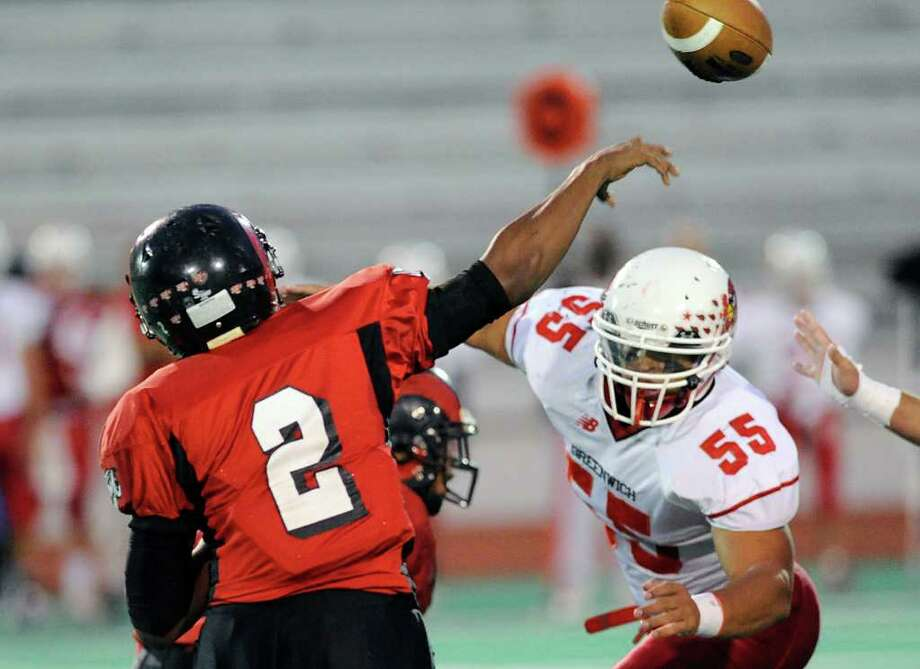 Bridgeport Central QB Damekus Carmon, # 2, passes while being pressured by Kyle Camacho # 55 of Greenwich High School during football game between Greenwich High School and Bridgeport Central High School at Kennedy Stadium, Bridgeport, Friday night, Oct. 21, 2011. Photo: Bob Luckey / Greenwich Time