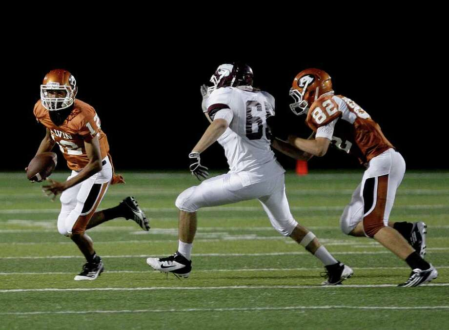 Running back Aaron Jackson #12 of the Alvin Yellowjackets scrambles as lineman Fabricio Cabrera #65 of the Clear Creek Wildcats  gives chase in a high school football game at Alvin Memorial Stadium in Alvin, Texas. For the Chronicle: Thomas B. Shea Photo: For The Chronicle: Thomas B. She