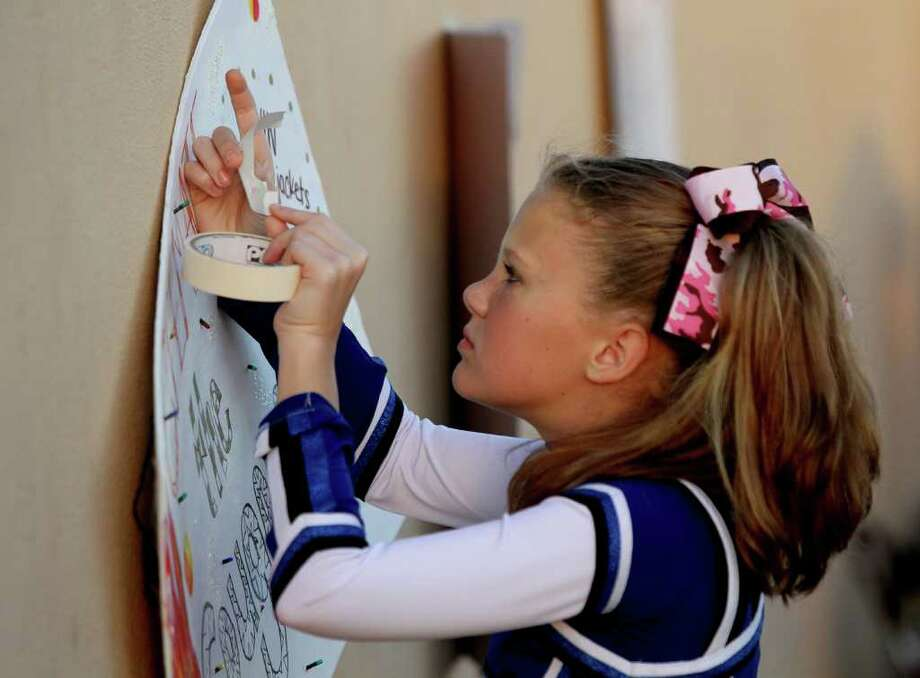 Fairview Jr. High cheerleader Brenna Jernigan hangs a Yellowjackets poster up before Clear Creek Wildcats played against the Alvin Yellowjackets in a high school football game at Alvin Memorial Stadium in Alvin, Texas. For the Chronicle: Thomas B. Shea Photo: For The Chronicle: Thomas B. She