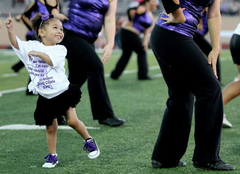 Two year old Audrey Simmons, dances with the Alvin Decateers dance team before Clear Creek Wildcats played against the Alvin Yellowjackets in a high school football game at Alvin Memorial Stadium in Alvin, Texas. For the Chronicle: Thomas B. Shea Photo: For The Chronicle: Thomas B. She