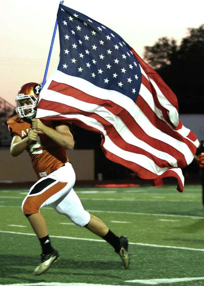 Jackson Basiliere #2 of the Alvin Yellowjackets carries out the American flag while running onto the field before the Yellowjackets played against the Clear Creek Wildcats of the  in a high school football game at Alvin Memorial Stadium in Alvin, Texas. For the Chronicle: Thomas B. Shea Photo: For The Chronicle: Thomas B. She