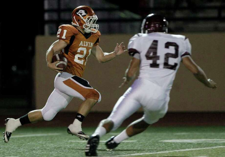 Kickoff return man John McDowell #21 of the Alvin Yellowjackets runs past Brandon Peters #42 of the Clear Creek Wildcats  in a high school football game at Alvin Memorial Stadium in Alvin, Texas. For the Chronicle: Thomas B. Shea Photo: For The Chronicle: Thomas B. She