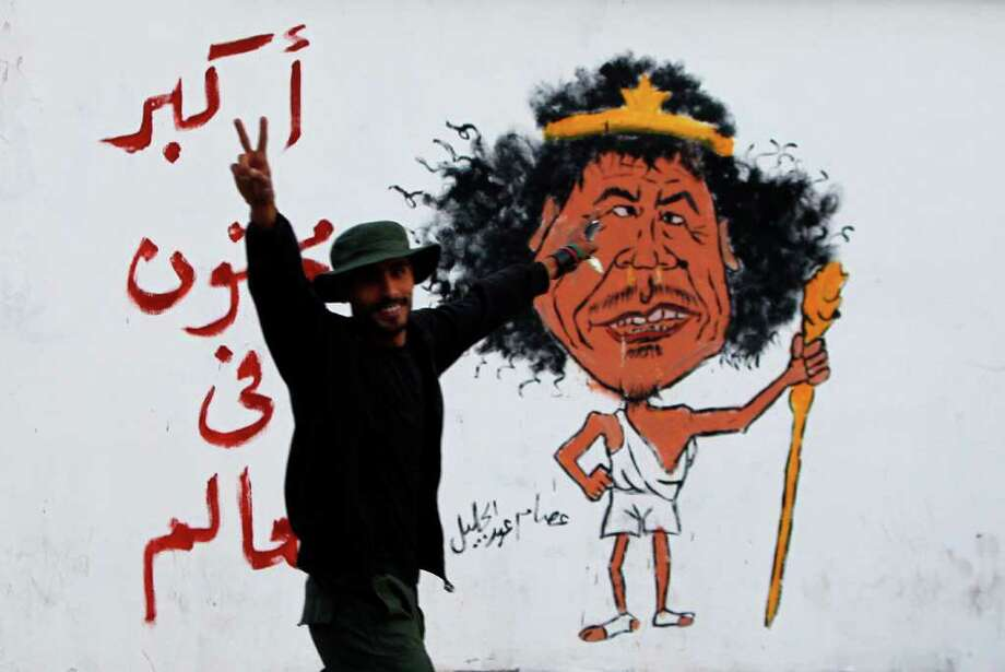 "A Libyan man gestures front of a graffiti reading: ""The greatest Crazy of the World"" in Tripoli, Libya, Friday Oct. 21, 2011. The death Thursday of Gadhafi, two months after he was driven from power and into hiding, decisively buries the nearly 42-year regime that had turned the oil-rich country into an international pariah and his own personal fiefdom. Photo: Francois Mori, Associated Press / AP"