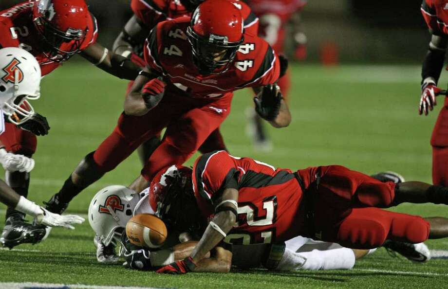 North Shore's Brodrick Thomas (22) fights over a fumbled kickoff with La Porte's Aaron Nance-Garrett during the first half of a high school football game, Friday, October 21, 2011 at Galena Park Stadium in Houston. North Shore recovered the fumble, and scored a touchdown on the ensuing drive. Photo: Eric Christian Smith, For The Chronicle