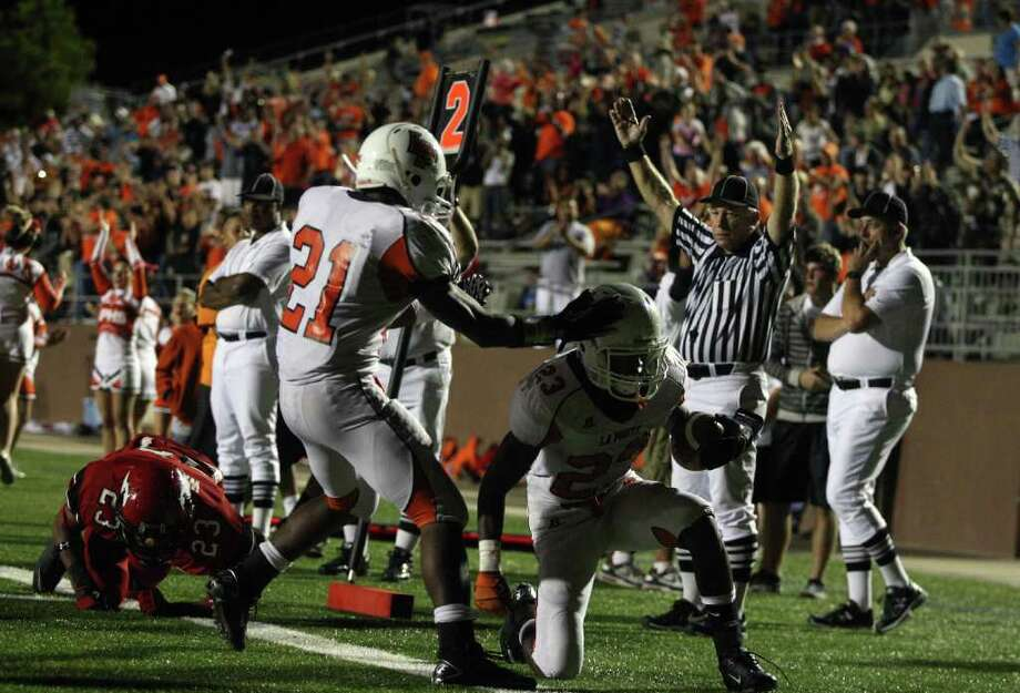 La Porte's Keith Whitley (21) congratulates Johnathan Lewis after Lewis scored a touchdown during the first half of a high school football game against North Shore, Friday, October 21, 2011 at Galena Park Stadium in Houston. Photo: Eric Christian Smith, For The Chronicle