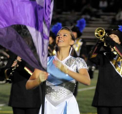 Jenna Kavulich twirls a flag during the Bunnell marching band and Color Guard perfomance at  Bunnell High School
