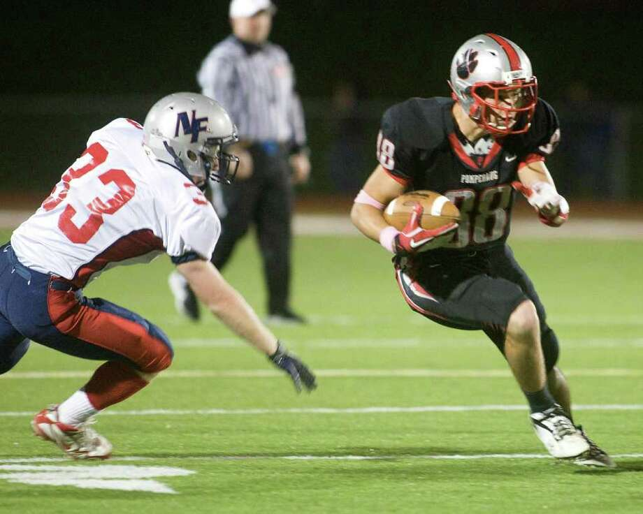 Pomperaug High School's Brett Gaughan evades New Fairfield's James Colella after catching a pass during their SWC football game Friday night, Oct. 21, 2011 at Pomperaug High School in Southbury. Photo: Barry Horn / The News-Times Freelance