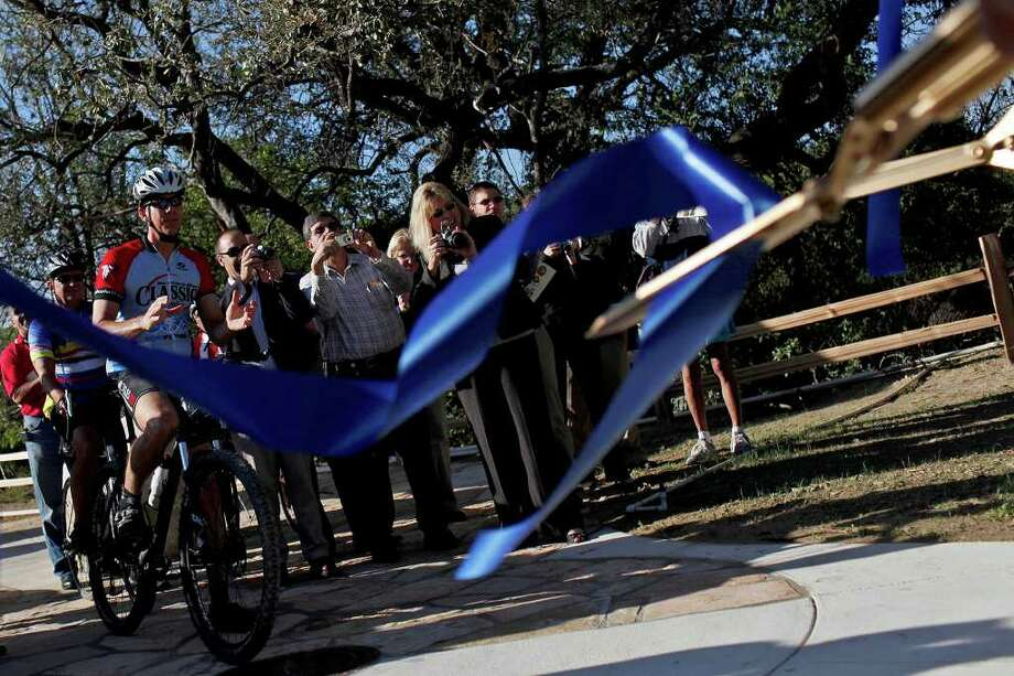 Bystanders and officials celebrate the cutting of a ribbon to officially open the central segment of the Leon Creek Greenway in San Antonio on Friday, Oct. 21, 2011. Photo: Lisa Krantz/lkrantz@express-news.net / SAN ANTONIO EXPRESS-NEWS