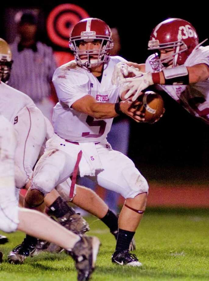 Bethel High School quarterback Brandon Schmidt hands off the football in a game against Joel Barlow, played at Barlow. Friday, Oct. 21, 2011 Photo: Scott Mullin
