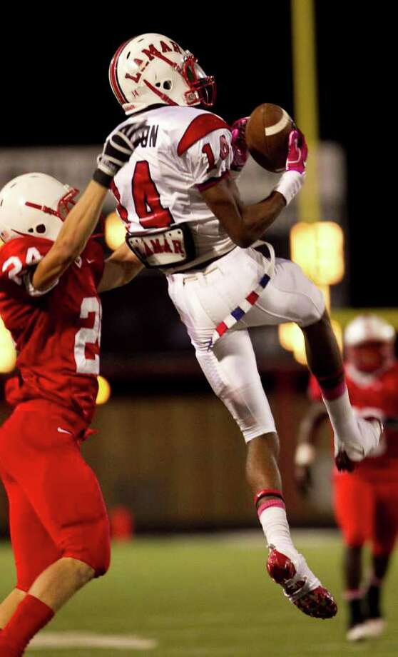 Lamar High School's Carrington Thompson (14) makes a big catch to put the Cardinals in good field position as Bellaire High School's Jacoby James Dean tries to cover during the fourth quarter of a 20-5A high school football game, Friday, Oct. 21, 2011, at Butler Stadium in Houston. Lamar High School won 20-16. Photo: Nick De La Torre, Houston Chronicle / © 2011  Houston Chronicle