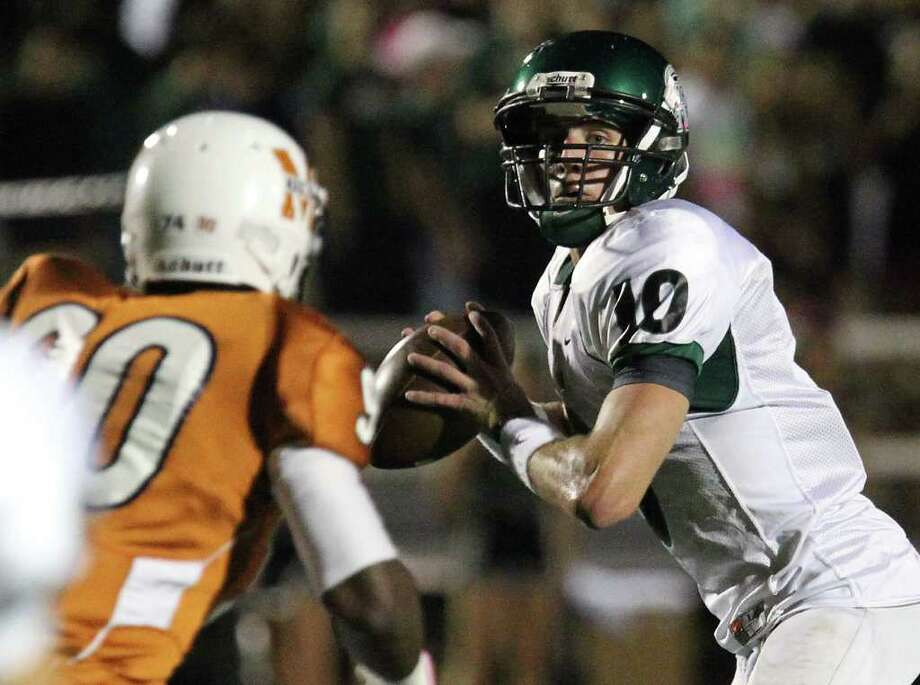 Reagan's Trevor Knight (10) drops back for a pass against Madison's Isaiah Carter (90) in the first half of football at Comalander Stadium on Friday, Oct. 21, 2011. Kin Man Hui/kmhui@express-news.net Photo: Kin Man Hui, ~ / San Antonio Express-News