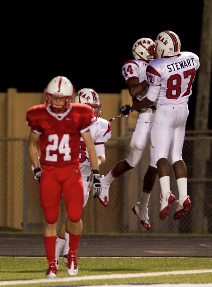 Lamar High School's Carrington Thompson (14) and Joshua Stewart (87)celebrates Thompsons touchdown as Bellaire High School's Jacoby James Dean (24) walks back to his bench during the third quarter of a 20-5A high school football game, Friday, Oct. 21, 2011, at Butler Stadium in Houston. Lamar High School won 20-16. Photo: Nick De La Torre, Houston Chronicle / © 2011  Houston Chronicle