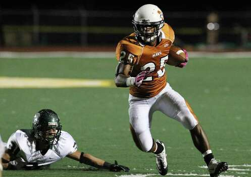 Madison's Galen McAllister (25) hustles for yardage against Reagan's Daerek Wilson (31) in the first half of football at Comalander Stadium on Friday, Oct. 21, 2011. Kin Man Hui/kmhui@express-news.net Photo: Kin Man Hui, ~ / San Antonio Express-News