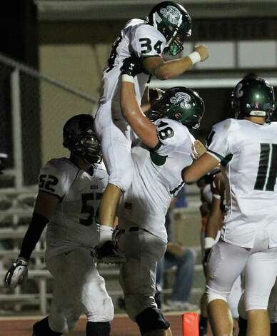 Reagan's Michael Coppage (34) gets lifted up by Matt Beyer (78) after Coppage scored the final touchdown to seal their win against Madison in the second half of football at Comalander Stadium on Friday, Oct. 21, 2011. Reagan defeated Madison, 38-17. Kin Man Hui/kmhui@express-news.net Photo: Kin Man Hui, ~ / San Antonio Express-News