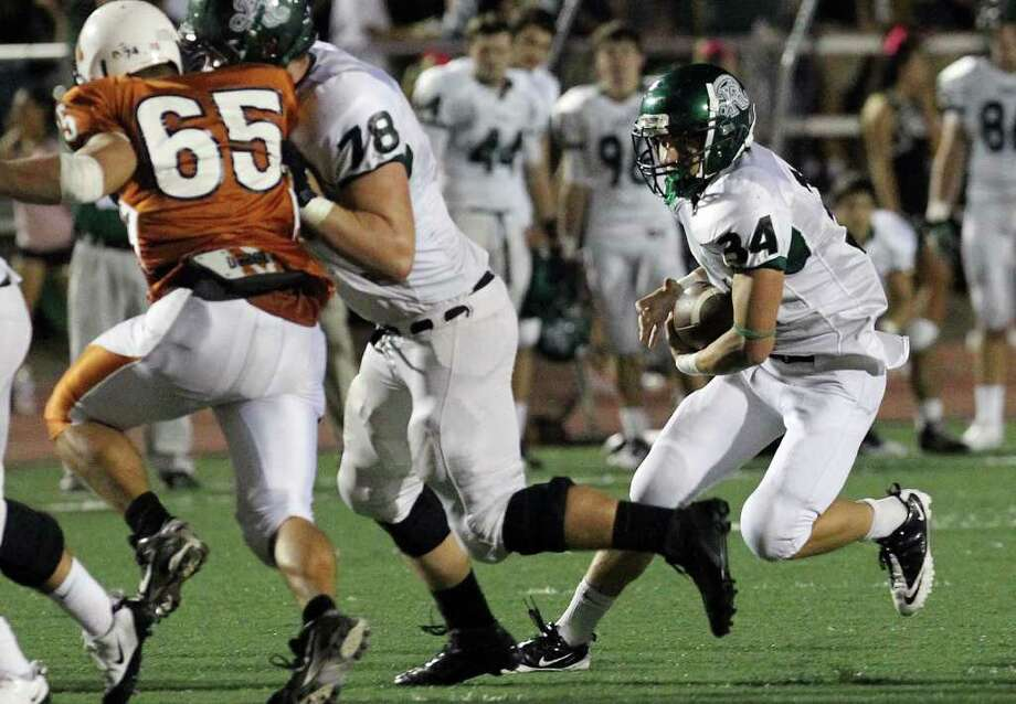 Reagan's Michael Coppage (34) runs behind the blocking of Matt Beyer (78) against Madison's Dylan Zera (65) in the second half of football at Comalander Stadium on Friday, Oct. 21, 2011. Reagan defeated Madison, 38-17. Kin Man Hui/kmhui@express-news.net Photo: Kin Man Hui, ~ / San Antonio Express-News