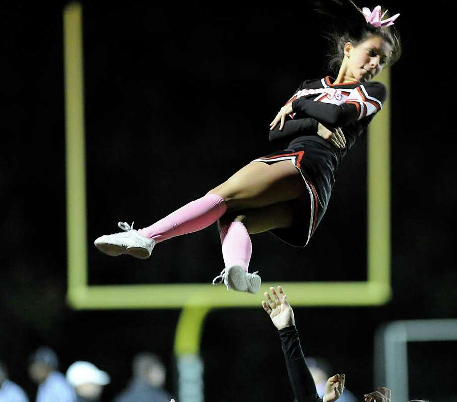 Warde Cheerleader Madison Beerbower flys through the air during high school football game between Fairfield Warde High School and Trinity Catholic High School, at Fairfield Warde, Friday night, Oct. 21, 2011. Photo: Bob Luckey / Greenwich Time