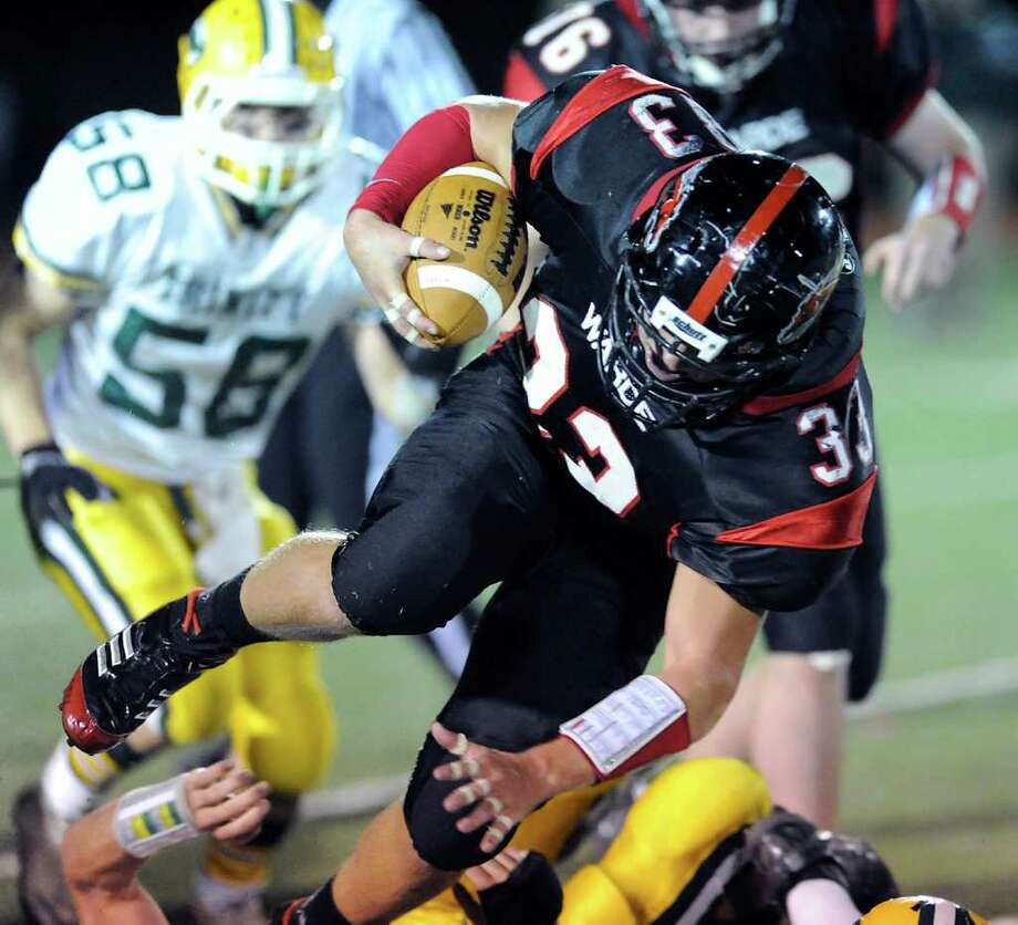 David Wolff of Fairfield Warde High School, # 33 in action during football game between Fairfield Warde High School and Trinity Catholic High School, at Fairfield Warde, Friday night, Oct. 21, 2011. Rushing is # 58 Dan Pason of Trinity Catholic. Photo: Bob Luckey / Greenwich Time