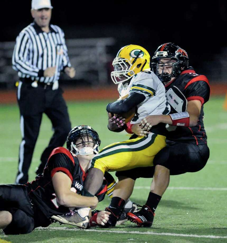 At center, Mike Davis of Trinity Catholic is tackled during high school football game between Fairfield Warde High School and Trinity Catholic High School, at Fairfield Warde, Friday night, Oct. 21, 2011. Photo: Bob Luckey / Greenwich Time