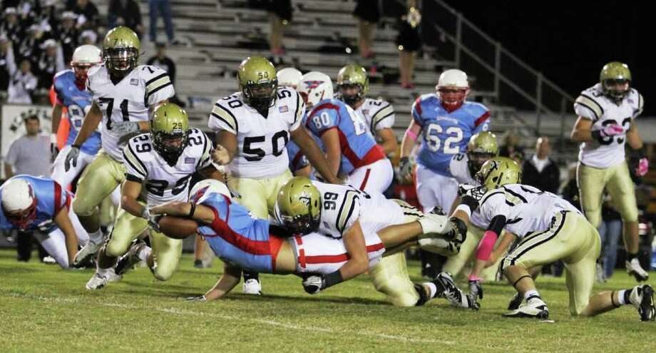 Raider running back Clay Choate stretches for extra yardage as he is brought down by Bulldog Corbin Carr and a host of other Nederland defenders in Lumberton Friday night.  Photo provided by Kevin Daigle Photo: Kevin Daigle