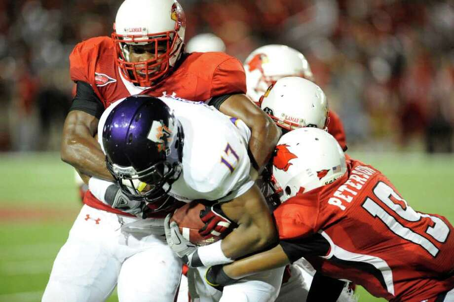 Cardinals linebackers Asim Hicks, left, and Kennon Peterson (19) combine for the tackle against  Northwestern State's Louis Hollier (17) in the first half at Provost Umphrey Stadium. Saturday, October 8, 2011.  Valentino Mauricio/The Enterprise