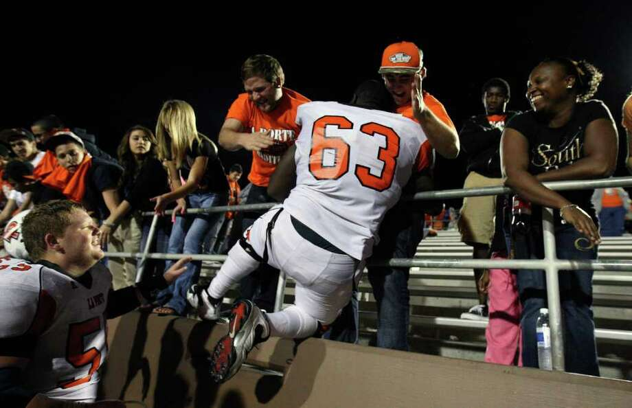 La Porte's Cory Lee (63) celebrates with students Tyler O'Daniel (right) and Stan Dillon the Bulldogs' 38-30 victory over North Shore, Friday, October 21, 2011 at Galena Park Stadium in Houston. Photo: Eric Christian Smith, For The Chronicle