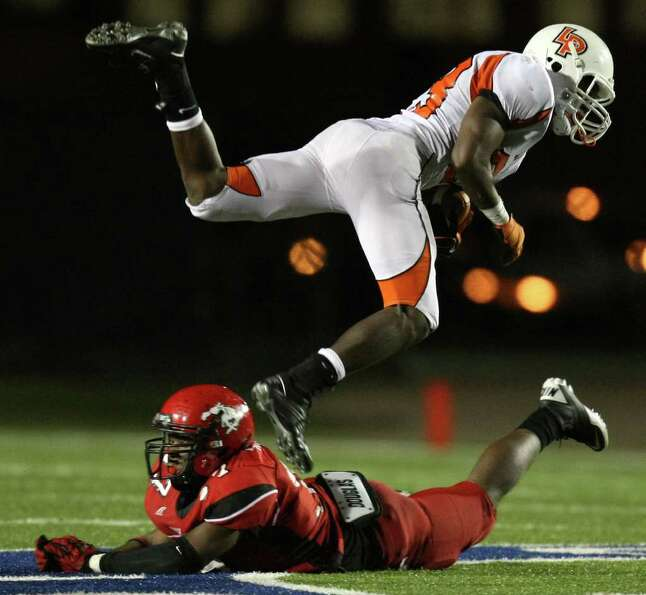 La Porte's Johnathan Lewis (23) leaps over North Shore's Jarius Moore during the second half of a hi