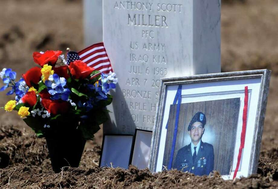 A portrait of Anthony Scott Miller, who, at age 19, became the first San Antonio casualty in Operation Iraqi Freedom, rests by his headstone at Fort Sam Houston National Cemetery on Tuesday, April 7, 2009. Photo: BILLY CALZADA, BILLY CALZADA/GCALZADA@EXPRESS-NEWS.NET / gcalzada@express-news.net