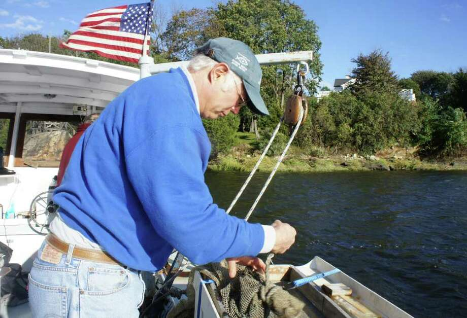 Earthplace Associate Director Pete Fraboni unties the net of a beam trawler aboard the RV Annie on the Saugatuck River on Thursday, Oct. 20, 2011. Photo: Paul Schott / Westport News