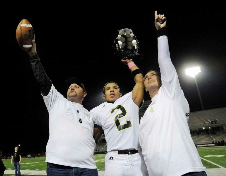 Celly Thomas, center, with his parents, Sammy Hampshire, holding the game ball, left, and Brandee Hampshire, celebrate the Pirates 28-15 win over Central at the BISD Thomas Center on Friday. The Pirates played their first game without senior player Matt Thomas, who died after being hit by a train on Sunday.  Friday, October 21, 2011.  Valentino Mauricio/The Enterprise Photo: Valentino Mauricio