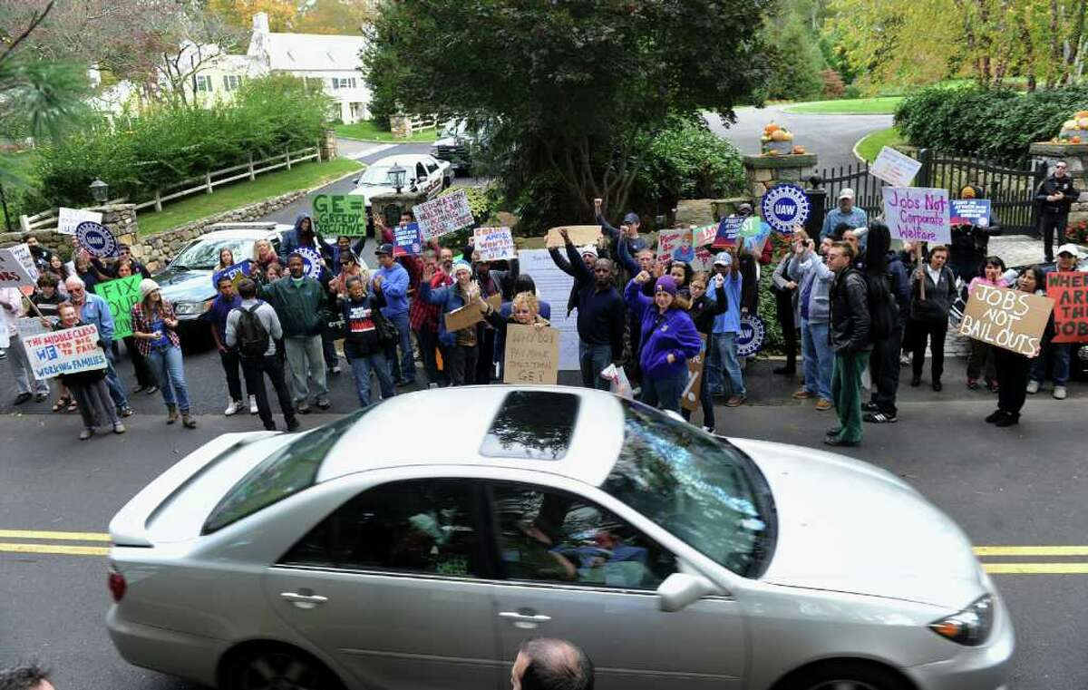 Members and supporters of Connecticut Working Families stand in front of GE CEO Jeff Immelt's home, in New Canaan, Conn. to protest on October 22, 2011.