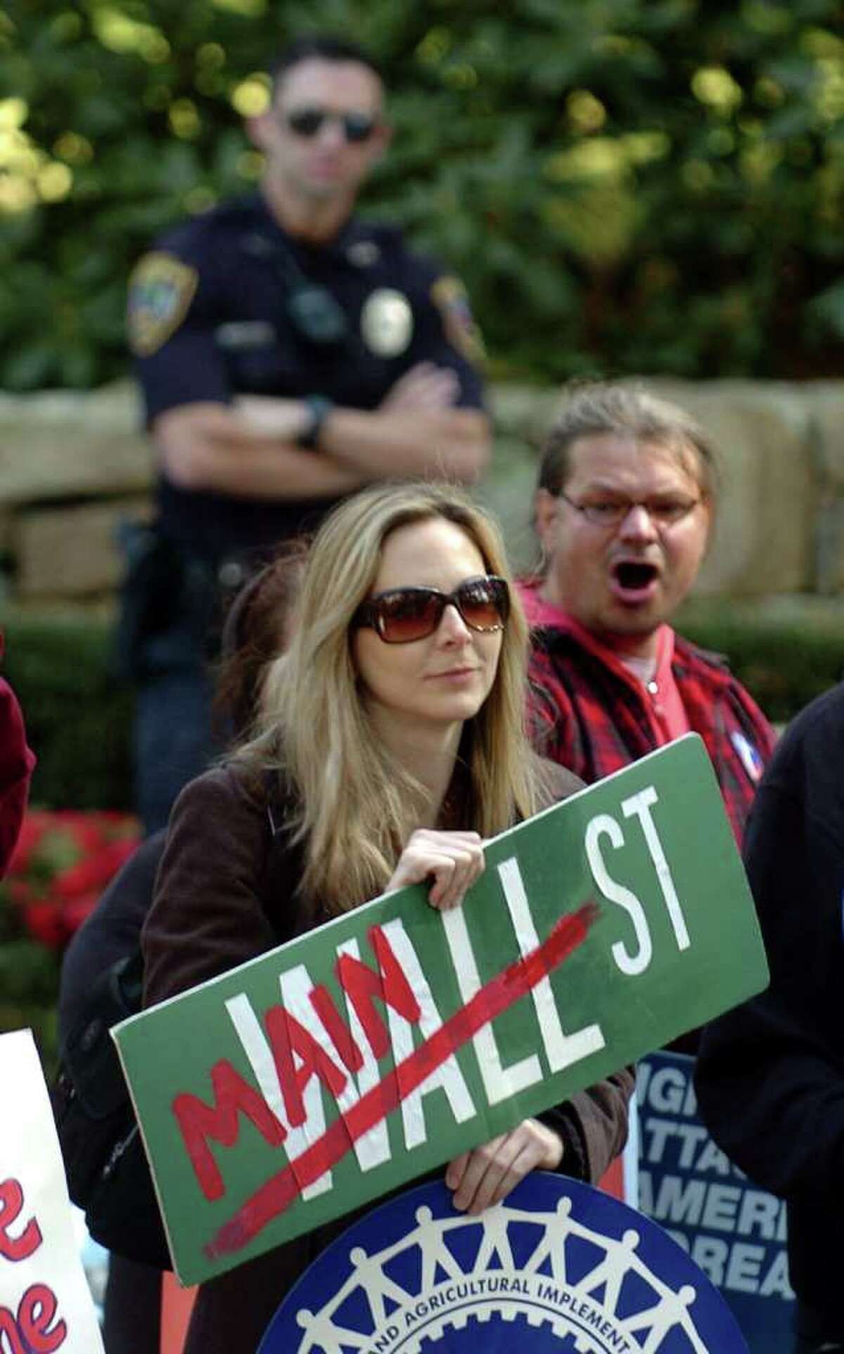 Katie Hern, of West Hartford, stands in front of GE CEO Jeff Immelt's home, in New Canaan, Conn. to protest with others from Connecticut Working Families on October 22, 2011.