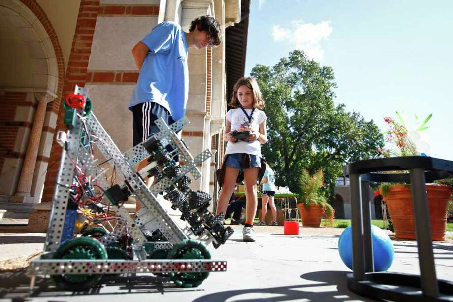 Ema Fosdick, 7, (right) experiments with a remote controlled robot as Martin Nikoltchev, 17, (left) gives instructions during the Sally Ride Science Festival at Rice University's Duncan Hall, Saturday, Oct. 22, 2011, in Houston. 