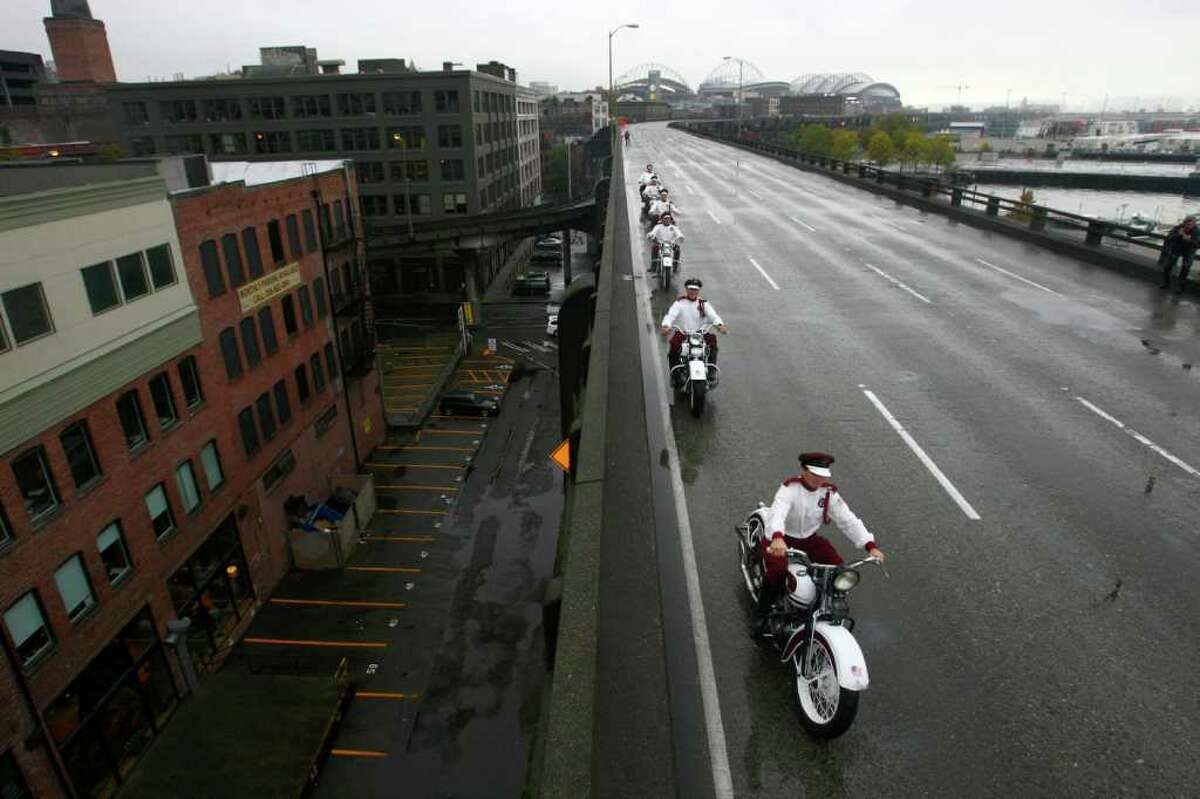 Members of the Seattle Cossacks classic motorcycle stunt team perform on the upper deck of the closed Alaskan Way Viaduct. The Cossacks performed their signature tricks on the highway for half an hour during the beginning of its nine day closure.