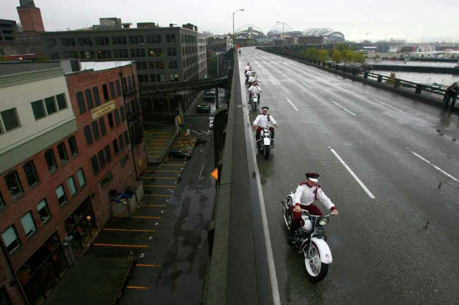 Members of the Seattle Cossacks classic motorcycle stunt team perform on the upper deck of the closed Alaskan Way Viaduct. The Cossacks performed their signature tricks on the highway for half an hour during the beginning of its nine day closure. Photo: JOSHUA TRUJILLO / SEATTLEPI.COM