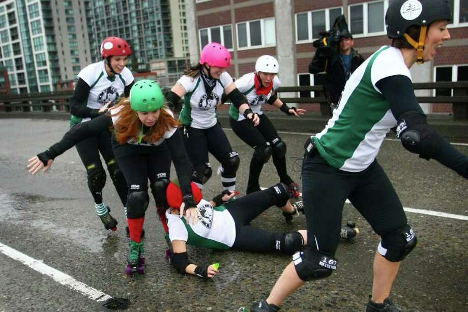 A member of the Rat City Rollergirls falls as they skate on the slippery upper deck of the closed Alaskan Way Viaduct. Photo: JOSHUA TRUJILLO / SEATTLEPI.COM