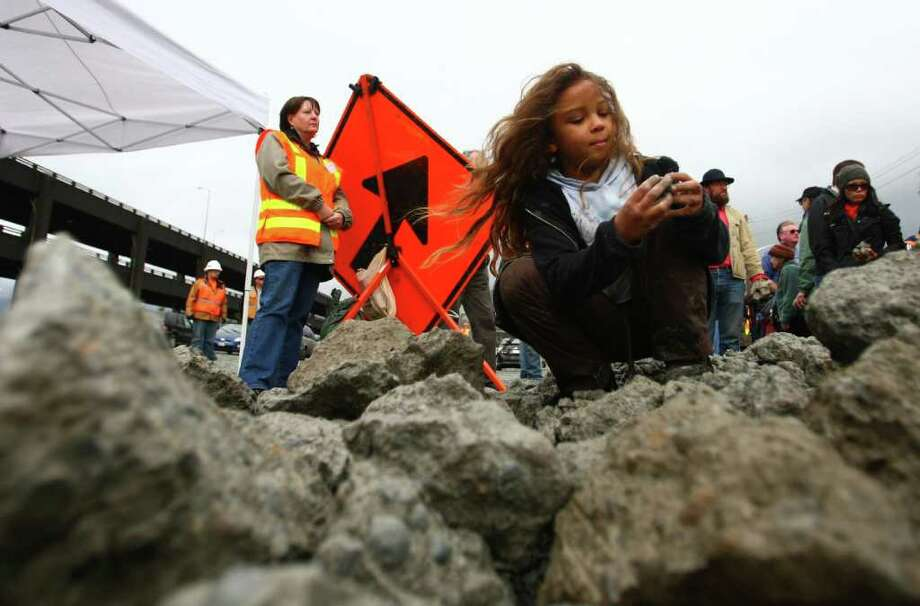 Noni Bayly, 7, searches for the perfect souvenir of the Alaskan Way Viaduct in a pile of rubble from the demolition. Photo: JOSHUA TRUJILLO / SEATTLEPI.COM