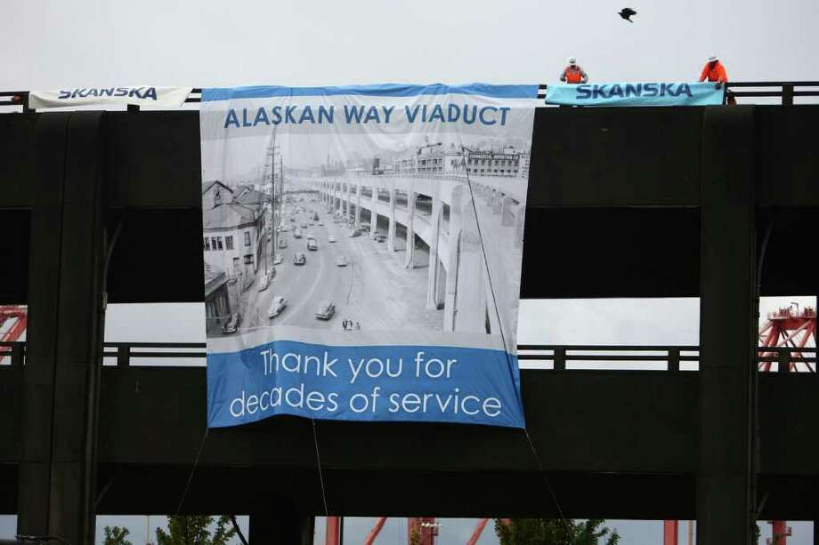 Workers hang a banner on the Alaskan Way Viaduct as the aging structure begins to come down on Saturday. Photo: JOSHUA TRUJILLO / SEATTLEPI.COM