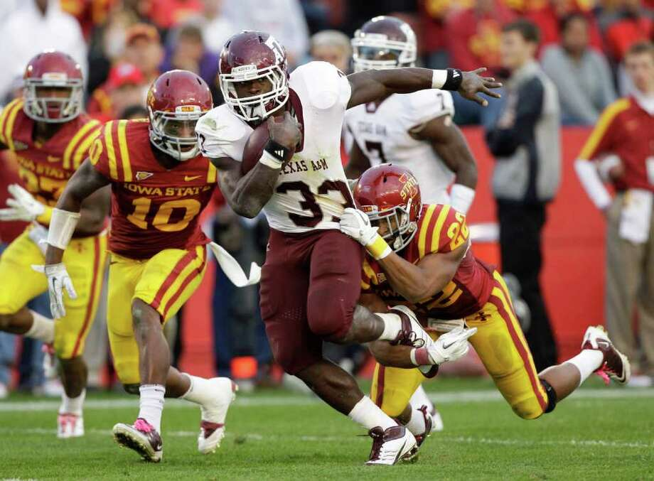 Texas A&M running back Christine Michael (33) runs from Iowa State defensive back Jacques Washington (10) and defensive back Ter'Ran Benton (22) during the second half of an NCAA college football game Saturday, Oct. 22, 2011, in Ames, Iowa. Texas A&M won 33-17. (AP Photo/Charlie Neibergall) Photo: Charlie Neibergall, Associated Press / AP