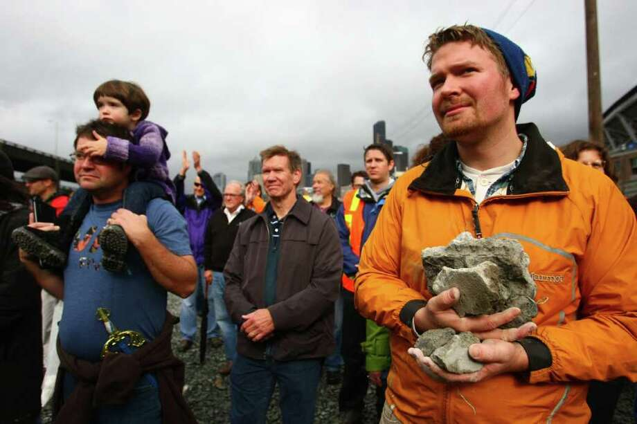 Christopher Hanson holds onto souveniers of the Alaskan Way Viaduct on Saturday during a celebration marking the beginning of its demolition. Photo: JOSHUA TRUJILLO / SEATTLEPI.COM